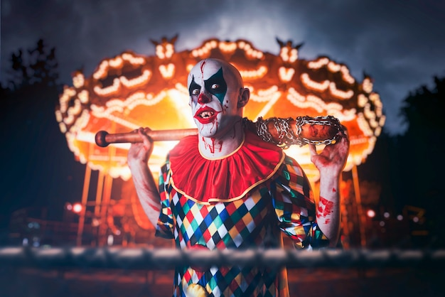 Crazy bloody clown with baseball bat in the amusement park. man with makeup in halloween costume, scary killer