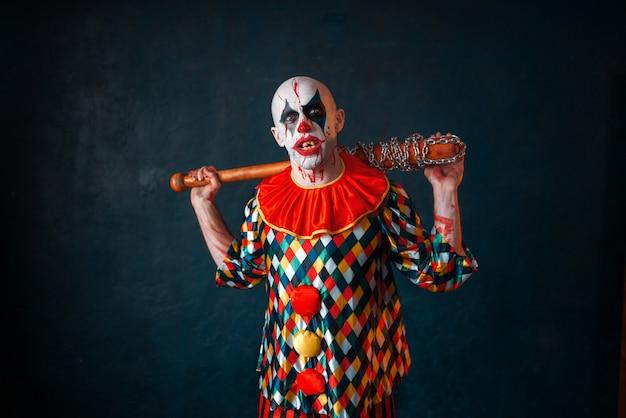 野球のバットを持つ狂気の血まみれのピエロ。ハロウィーンの衣装、マニアックなメイクを持つ男