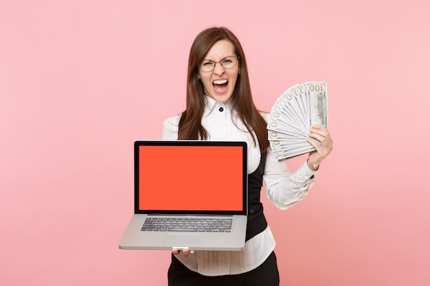 Crazy business woman screaming holding bundle lots of dollars, cash money and laptop pc computer with blank empty screen isolated on pink background. lady boss. achievement career wealth. copy space.