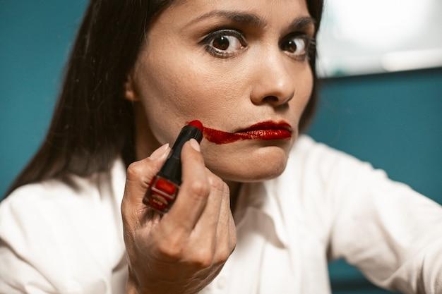 Сумасшедшая деловая женщина с красной помадой, делать макияж на работе