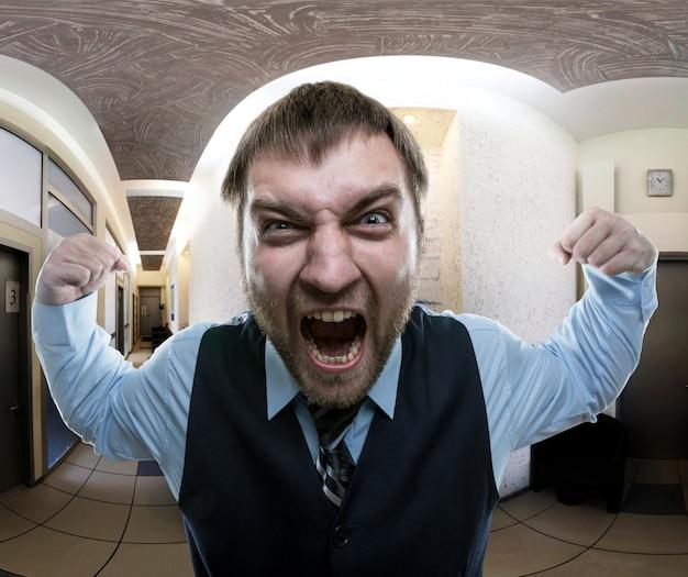 Сумасшедший бизнесмен кричит в офисе