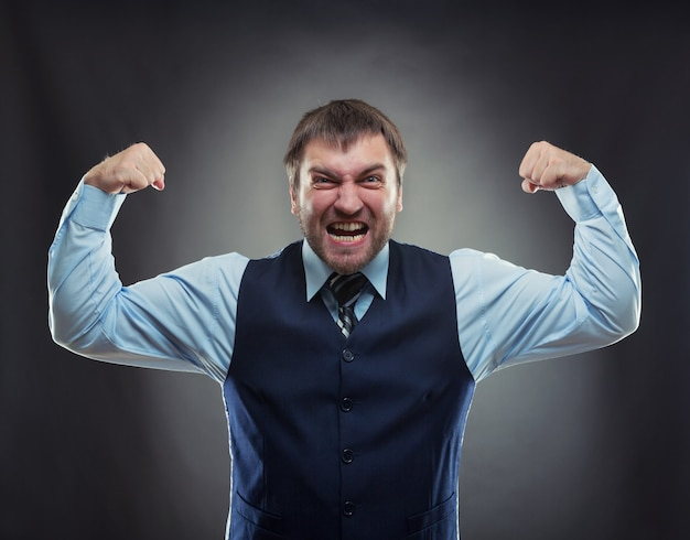 Crazy businessman shows his muscles