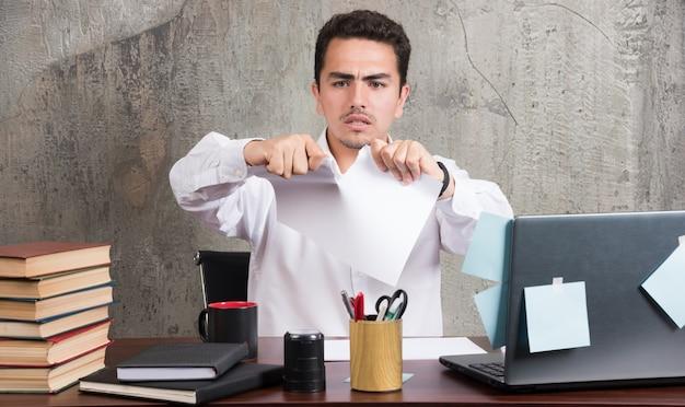 Uomo d'affari pazzo che divide la carta alla scrivania dell'ufficio.