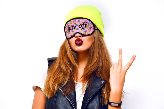 Crazy cheeky hipster woman s wearing neon hat and funny sleeping eye mask. urban swag style, sending kiss, dark trendy lipstick, yo science, flash.