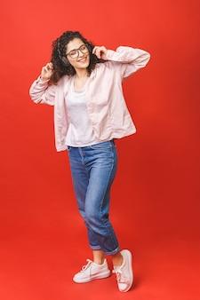 踊りながら音楽を聴くイヤホンでカジュアルでクレイジー陽気な女の子