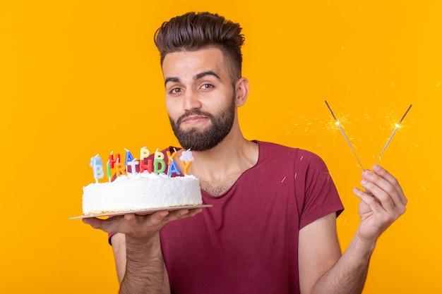 그의 손에 불타는 촛불과 노란색 배경에 축하 집에서 만든 케이크를 들고 미친 쾌활 한 젊은 남자. 생일 및 기념일 축 하 개념입니다.