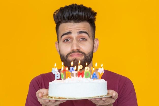 그의 손에 불타는 촛불과 축하 수제 케이크를 들고 미친 쾌활한 젊은 남자