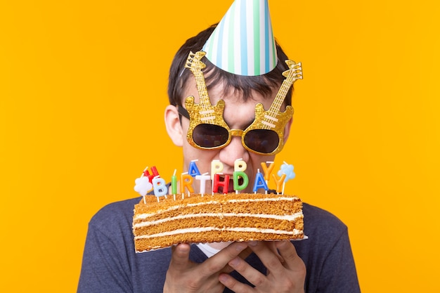 Crazy cheerful young man in glasses and paper congratulatory hats holding cake