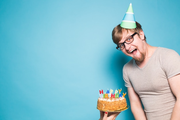Crazy cheerful young man in glasses and paper congratulatory hats holding cakes happy birthday standing on a blue wall. jubilee congratulations concept. promo space