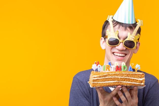 コピースペースと黄色の表面に立っているケーキお誕生日おめでとうを保持している眼鏡と紙のお祝いの帽子でクレイジー陽気な若い男