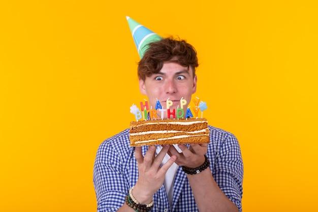 黄色い表面に立っているケーキお誕生日おめでとうを保持している紙のお祝いの帽子でクレイジー陽気な若い男
