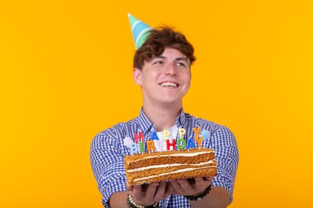 黄色の壁に立ってケーキお誕生日おめでとうを保持している紙のお祝いの帽子でクレイジー陽気な若い男。ジュビリーおめでとうコンセプト。