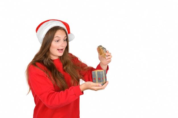 Сумасшедшая крутая веселая позитивная оптимистичная красивая женщина в новогодней шапке открывает рождественский подарок