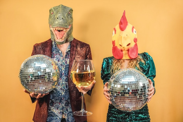 Crazy couple having fun celebrating new year eve party holding disco balls and glass of wine - focus on t-rex and chicken mask