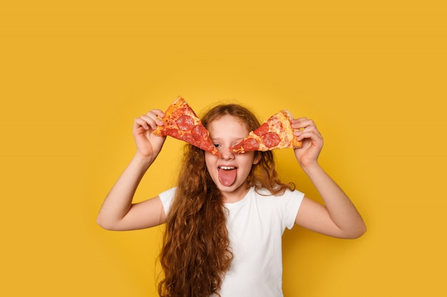 Crazy curly girl holds two slices of pizza near her eyes and sticks out her tongue.