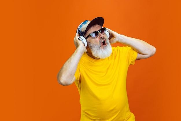 Безумный танец. портрет старшего хипстерского человека, использующего устройства, гаджеты, изолированные на оранжевом фоне студии. технология и радостная концепция образа жизни пожилых людей. модные цвета, вечная молодость. copyspace для вашей рекламы.