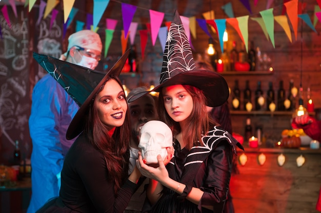 Crazy doctor and two beautiful witches celebrating halloween. witches with beautiful dresses.