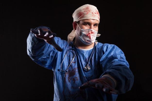 Сумасшедший доктор в маске хирурга и скрабах, залитых кровью на хэллоуин. опасный врач на черном фоне.