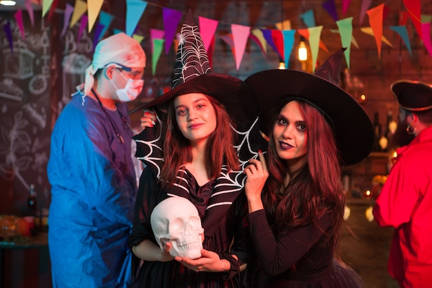 Crazy doctor with blood behind two beautiful witches at halloween party. halloween tradition.