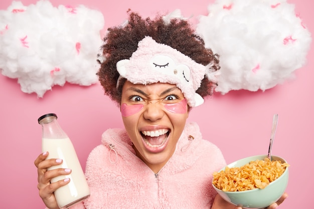 クレイジーな感情的なアフロアメリカ人女性は怒って叫び、柔らかいスリープマスクを身に着け、パジャマのポーズでコーンフレークのボウルとミルクが朝早く目が覚めるとイライラします