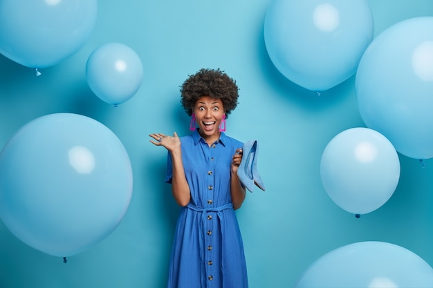 Crazy emotional curly woman looks happily , happy to get heeled shoes as present from husband, dressed in everything blue, inflated balloons around. people, dressing and partying concept