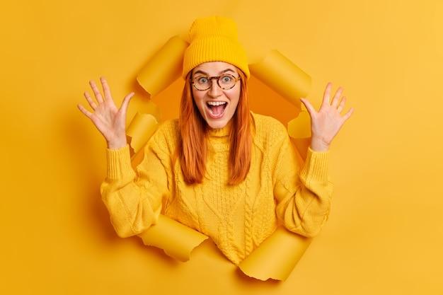 미친 감정적 인 빨간 머리 십대 소녀는 입을 넓게 열어 손바닥을 올려 멋진 뉴스에 반응하거나 큰 쇼핑 판매가 노란색 점퍼와 모자를 착용합니다.