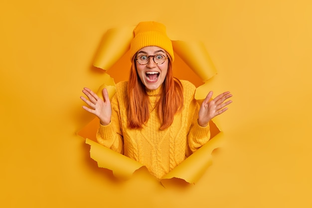Crazy emotional redhead young woman raises palms and exclaims loudly thrilled by hearing great news wears yellow hat knitted jumper.