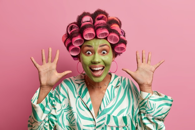 Crazy excited emotional woman looks with cheerful expression, keeps palms raised, smiles broadly, wears hair rollers, green beauty mask, wears casual robe