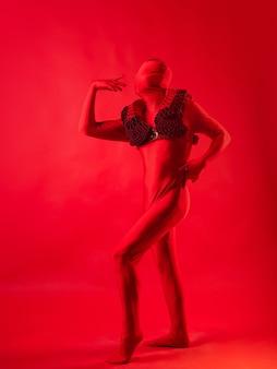 Безумная мода мужчина в красном купальнике на красной стене