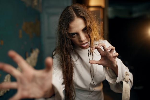 Сумасшедшая пациентка в смирительной рубашке в приступе ярости, психбольница.