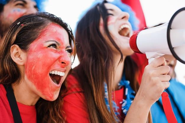 チームをサポートしながらドラムを演奏し、叫んでいるクレイジーなサッカーサポーター-左の女性に焦点を当てる