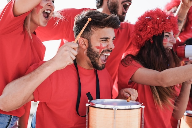 チームをサポートしながらドラムを演奏し、叫んでいるクレイジーなサッカーサポーター-男の顔に焦点を当てる