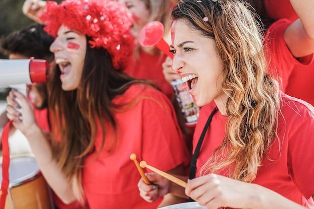 팀을 지원하면서 드럼을 연주하고 비명을 지르는 미친 축구 서포터-오른쪽 여성에게 집중