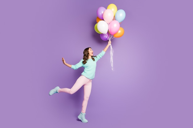 Crazy funky feminine girl hold hand catch many baloons flying sky scream wow omg wear soft pink pastel trousers pants footwear.
