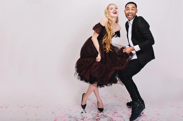 Безумный веселый праздник радостной влюбленной пары в роскошных вечерних нарядах, весело проводящих время вместе. улыбаться, выражать настоящие положительные эмоции, танцевать.
