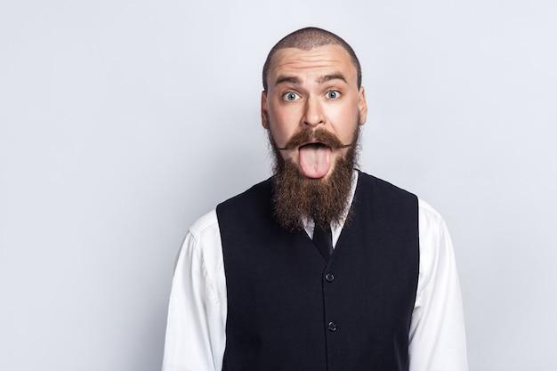 미친 웃긴 얼굴. 턱수염과 핸들바 콧수염을 가진 잘생긴 사업가가 혀를 내밀고 카메라를 쳐다보고 있습니다. 스튜디오 촬영, 회색 배경입니다.