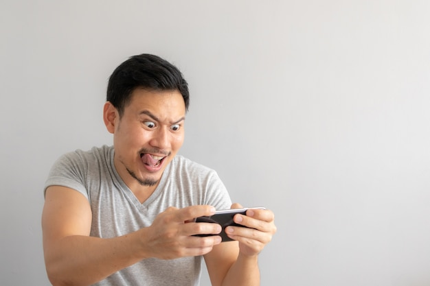 Crazy and funny face of man addicted to mobile game.