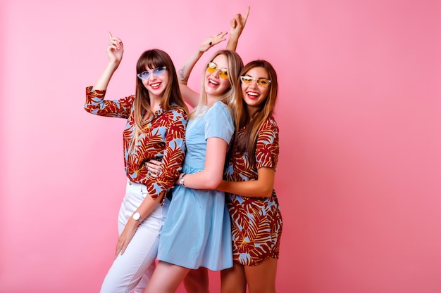 Crazy funny picture of three happy best friends girls enjoying party time together, dancing and laughing, color matching trendy elegant outfits and glasses, positive mood, pink wall