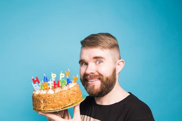 青い表面に立っている彼の手でお誕生日おめでとうケーキを保持しているクレイジー面白いポジティブな男のヒップスター