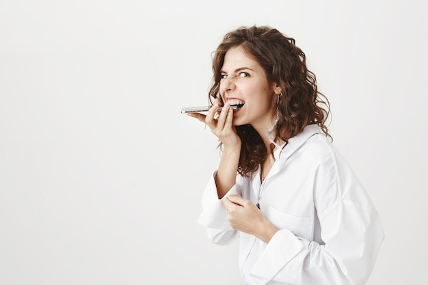 Crazy funny woman biting her mobile phone