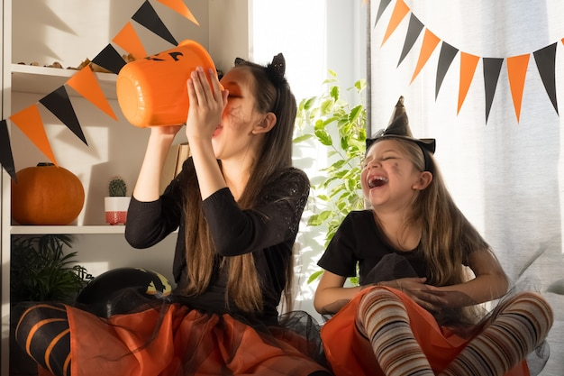 ハロウィーンの魔女の衣装を着た10歳と7歳のクレイジーな女の子の姉妹が休日を祝う