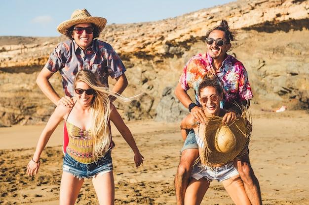 休暇中にビーチで一緒に遊んでいる白人の友人の男性と女性のクレイジーなグループ