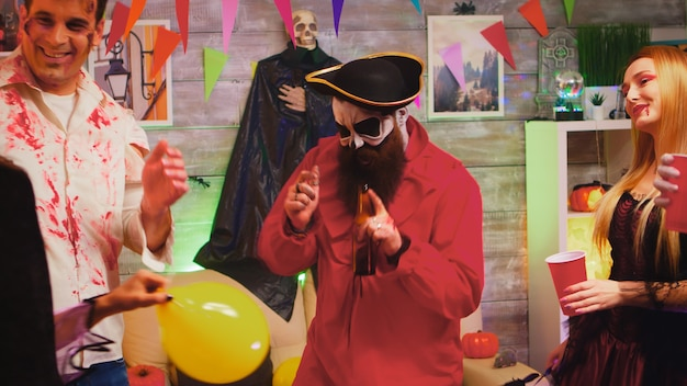 Crazy halloween party with different funny and scary characters dancing in decorated room. witch, repear, pirate and zombie