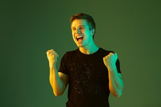 Crazy happe, 승리를 축하합니다. 네온 불빛에 녹색 스튜디오 배경에 고립 된 백인 남자의 초상화.