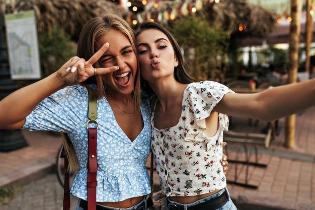 파란 꽃무늬 블라우스를 입은 미친 행복한 금발 여성이 윙크하고 활짝 웃고 평화의 표시를 보여줍니다