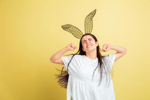 Безумно счастливы, танцуют. кавказская женщина как пасхальный кролик на желтом фоне студии. поздравления с пасхой.