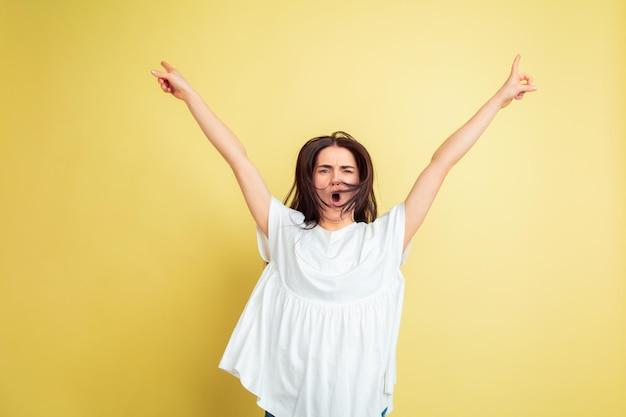 Безумно счастливы, танцуют. кавказская женщина как пасхальный кролик на желтом фоне студии.
