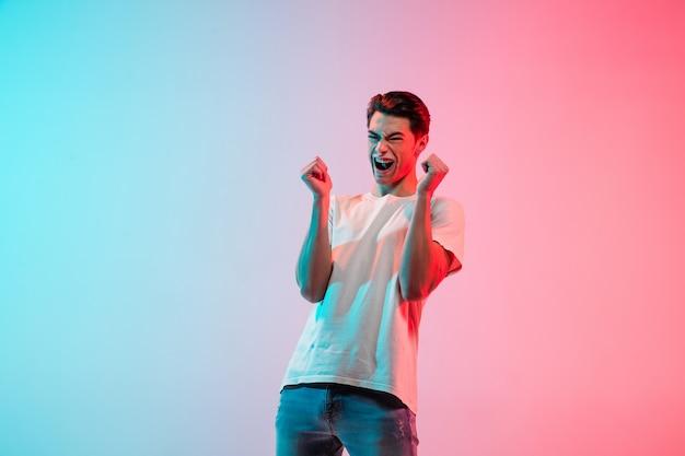 미친 행복, 미친. 네온 불빛에 그라데이션 블루 핑크 스튜디오 배경에 젊은 백인 남자의 초상화. 젊음, 인간의 감정, 표정, 판매, 광고의 개념. 절반 길이, copyspace입니다.