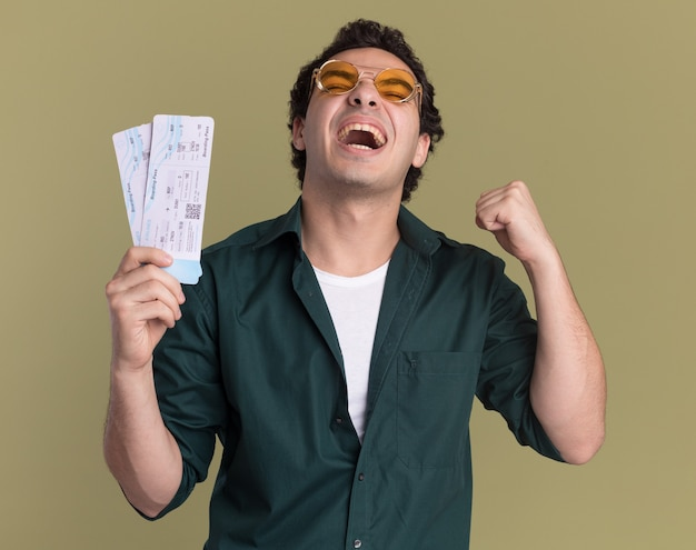 Crazy happy young man in green shirt wearing glasses holding air tickets clenching fist rejoicing his success standing over green wall