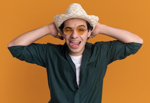오렌지 벽 위에 서있는 혀를 튀어 나와 정면을보고 안경을 쓰고 녹색 셔츠와 여름 모자에 미친 행복 한 젊은 남자